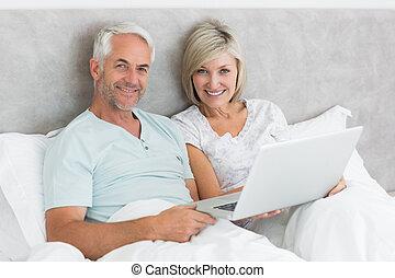 par, cama, maduras, usando computador portátil, feliz