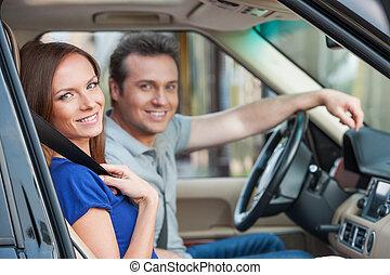 par cariñoso, en un coche, mirar, cámara, sonrisa dentuda