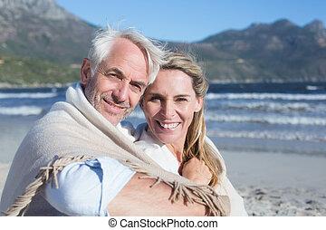 par, cobertor, sorrindo, sob, praia, sentando