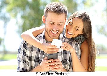 par, eller, kamrater skrattande, med, telefoner