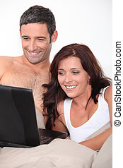 par en cama, con, computador portatil