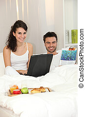 par en cama, con, un, computador portatil