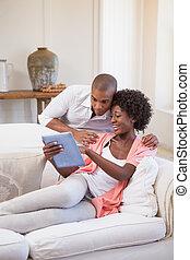 par feliz, relaxante, junto, sofá, usando, tabuleta