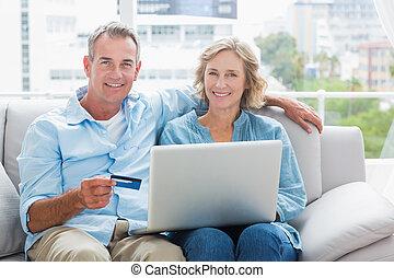 par feliz, sentando, ligado, seu, sofá, usando, a, laptop, comprar, online, sorrindo, câmera, casa, em, a, sala de estar