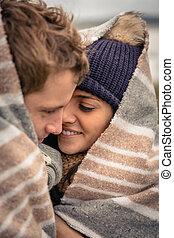 par jovem, abraçar, ao ar livre, sob, cobertor, em, um, gelado, dia