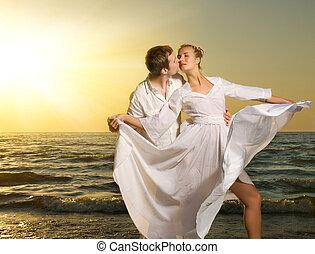 par jovem, apaixonadas, ligado, um, praia, em, pôr do sol