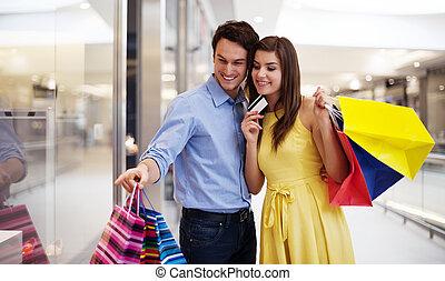 par jovem, apontar, janela fazendo compras