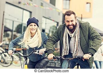 par jovem, bicicletas equitação, e, tendo divertimento, cidade