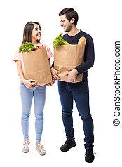 par jovem, com, mercearia, sacolas