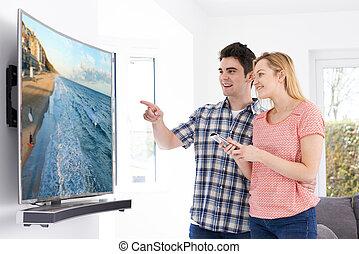 par jovem, com, novo, curvado, tela, televisão, casa