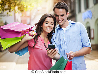 par jovem, com, saco shopping, usando, telefone móvel