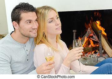 par jovem, desfrutando, um, bebida, pela lareira