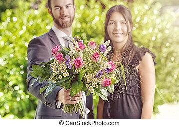 par jovem, em, a, jardim, com, buquê flores
