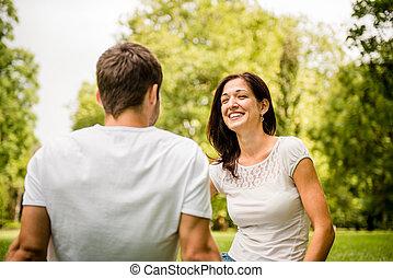 par jovem, falando, ao ar livre