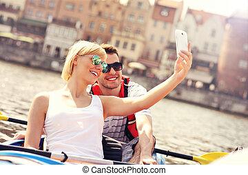 par jovem, fazendo exame retratos, em, um, canoa