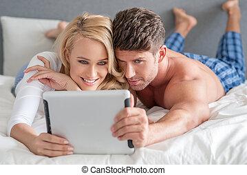 par jovem, leitura, um, tabuleta, cama