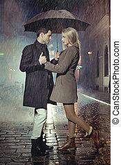 par jovem, posar, em, chuva pesada