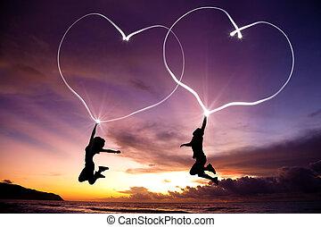 par jovem, pular, e, desenho, conectado, corações, por, lanterna, ar, praia, antes de, amanhecer