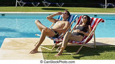 par jovem, relaxante, em, um, recorra piscina natação