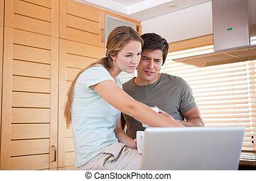 par jovem, tendo, chá, enquanto, usando, um, laptop