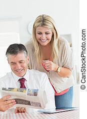 par, lendo um jornal, junto