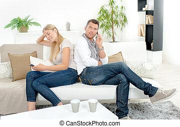 par, ligado, sofá, cada, usando, seu, cellphone
