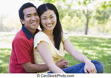 par, sentando, sorrindo, ao ar livre