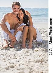 par, sentando, sorrindo, câmera, abraçar, areia
