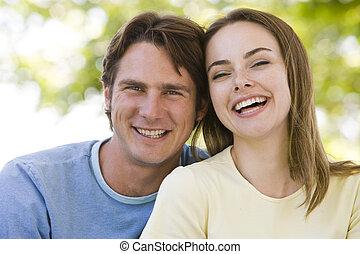 par, sorrindo, ao ar livre