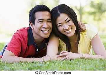 par, sorrindo, mentindo, ao ar livre