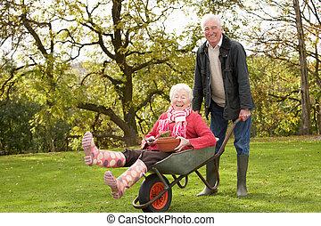 par velho, homem, dar, mulher, passeio, em, carrinho de mão