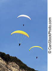 Para gliders - Three para gliders floating above a mountain...