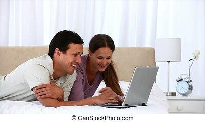 para, laptop, śliczny, używając, leżący, łóżko