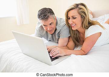 para, laptop, oglądając, leżący, łóżko, szczęśliwy