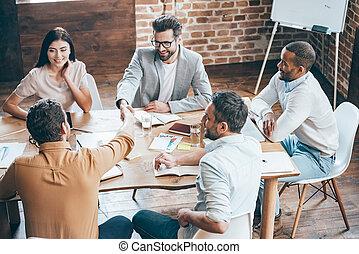 parabéns, com, seu, promotion!, vista superior, de, dois homens, apertar mão, e, sorrindo, enquanto, seu, coworkers, sentar tabela, em, escritório