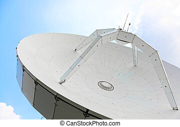 Parabolic antenna with clear blue sky on background -...
