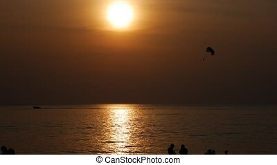 Parachute activity at tropical beach at sunset. Calm sea waters and. Beach recreations with parachute. Towing a parachute behind a boat over the sea. Silhouette of the parachute against the setting sun. Bright parachute on a background of a sky. 4k