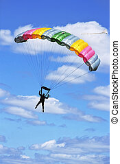 Facing a colored parachute on blue sky with clouds.