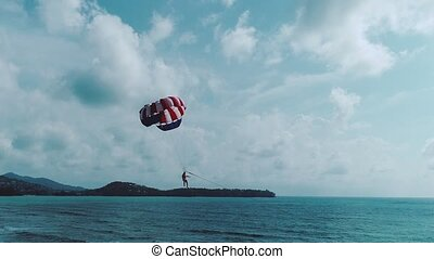Parachute flying above the sea - Man flying on a...