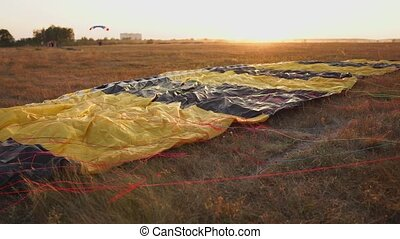 Parachute lying on the ground in the sunset rays of the sun...