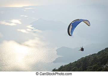 Parachute skydiver flying in clouds at top of mountains