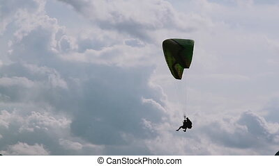Parachute sliding with two people in cloudly skyes