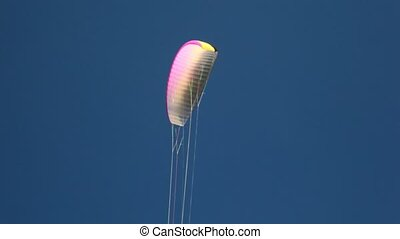 Parachute wing with colored lines flies in sky