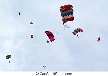 A group of skydivers parachuting their way down.