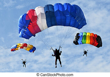 Three colorful parachutes on blue sky.