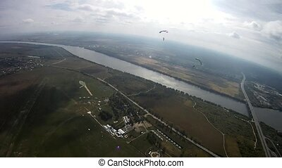 Parachutist flying above green field, river. Extreme active...