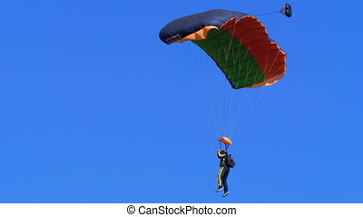 Parachutist flying with a parachute and landed on the ground. Skydiving. Summer day.