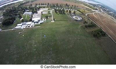Parachutist landing on green field. Extreme active sport....