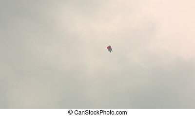 Parachutist soars in the sky.