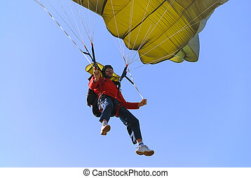 Parachutist pulling brakes of a green parachute.